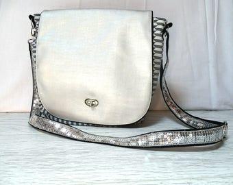 Messenger bag has flap with spangle metallic grey