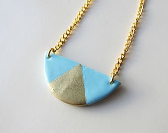 Minimalist graphic blue circle and triangle gold necklace