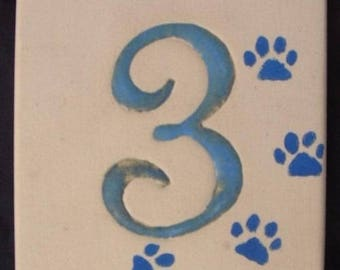 Blue front door number on a beige background, number 3, decorative cat paws