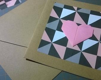 Carte origami, coeur rose sur fond géometrique