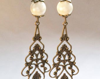 Earrings in brass with a white plastic bead