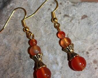 Stone earrings carnelian gems and golden color metal.