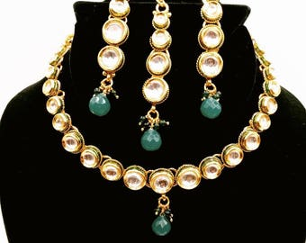 Indian necklace set kundan style with green bead in the center on the bottom