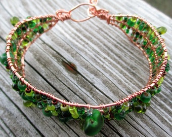 Copper wire wrapped bracelet beaded with variety of green glass beads and copper glass beads