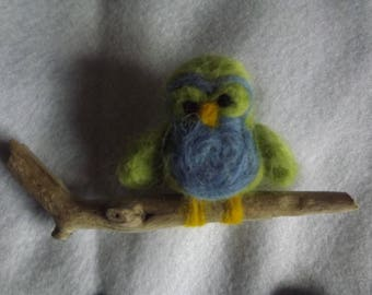 Little bright coloured felted owl sitting on a branch