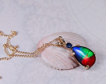 Ammolite pendant.A rainbow teardrop of rich colours set in gold with a sapphire companion.#080517