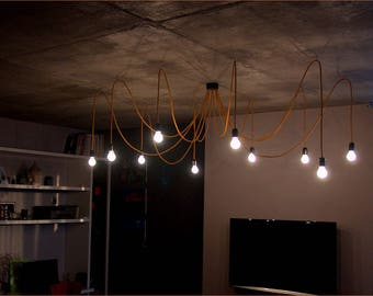 Golden chandelier with twelve textile cables. Ceiling octopus or spider.