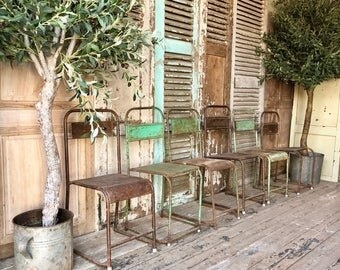 Six rustic, industrial style stacking chairs.