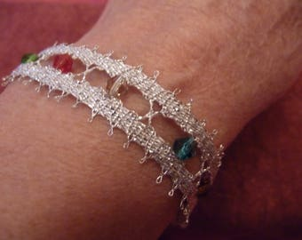 Bracelet made by traditional bobbin lace method, using silver coloured thread and coloured cristal beads.
