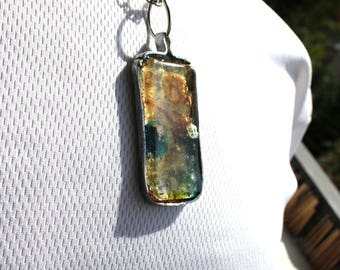 Pendant with resin with inclusions