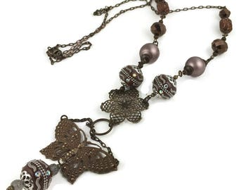 Long Boho Bead Necklace with Brass Butterfly and Filigree Accents.