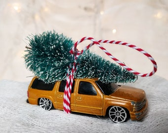 Gold SUV Matchbox Car with Tree Strapped to the Top Ornament by Distinguished Flamingo