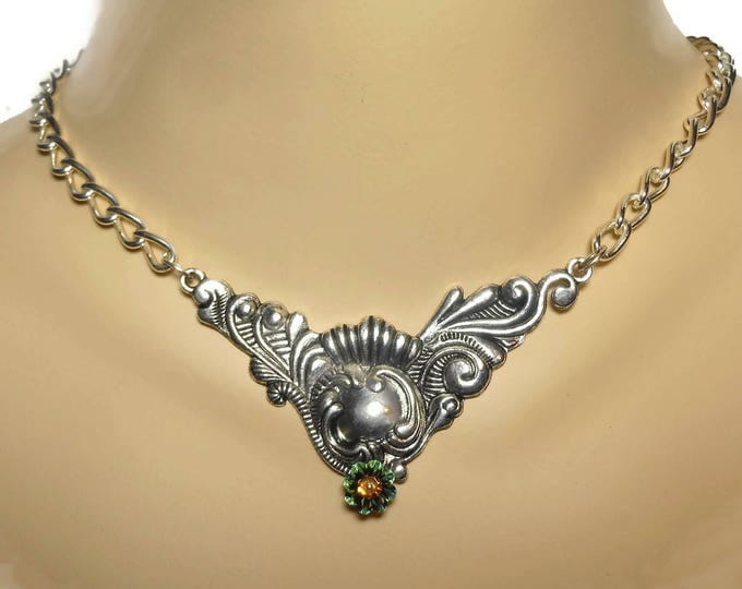 Silver plated swirl necklace, green Swarovski crystal marguerite lochrose flower below ornate focal with a eye catching plated curb chain