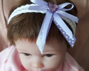 white headband with purple bows and purple heart-baby headband stretchy elastic with lilac ribbon bows and a purple heart gem-reborn