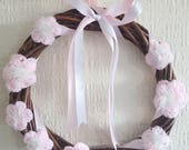 Image of Baby Pink Handmade Crochet Flowers with White and Irredescent Tinsel Yarn Centres on a Wreath Finished with Baby Pink and White Satin Ribbon