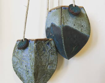 Textured ceramic hanging planter pot vase with two beads.
