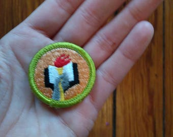 Small iron-on patch with torch and book