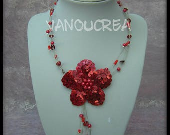 Red necklace made up of pearls and sequins flower