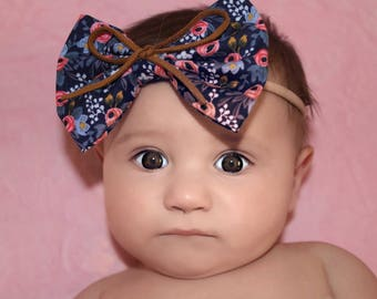 Floral fabric bow on thin brown elastic