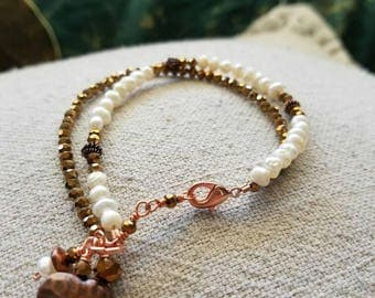 Layered bracelet with crystals , pearls,  and a copper charm
