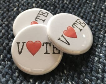 """Set of three 1.25"""" pinback buttons. Stand up for what you believe in. Be strong. Love conquers hate."""
