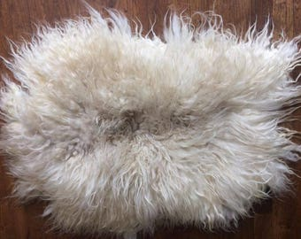 A handcrafted animal-friendly Leather-free felted Sheepskin with felt back.