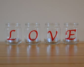 Set of 4 handpainted glass tea light holders with red paint spelling 'love'