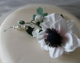 A single gum paste spray of blossom, anemones, ivy and pearl feature for a wedding cake