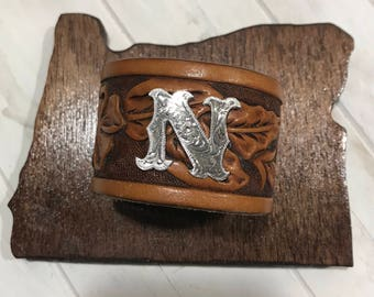 "Brown leather band with initial ""N"""