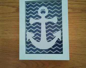 Shadow box for baby nursery in nautical vinyl anchor theme. Measures 5x7. Plastic casing , plexi glas top. Navy n white chevron background.