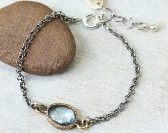 Oval faceted blue topaz bracelet in brass bezel setting and sterling silver oxidized rolo chain