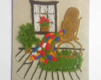 Vintage Yarn Art of a Yarn Plant beside a Wicker Rocker with a Colorful Quilt on a Green Rug -  Vintage Wall Art - Vintage Home Decor