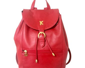 Vintage Paloma Picasso red leather backpack with golden logo motifs. Classic bag for unisex use.