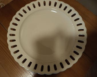 White ceramic plate with scalloped edges and lace like openings