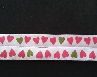 A pink ribbon with dark pink and green hearts