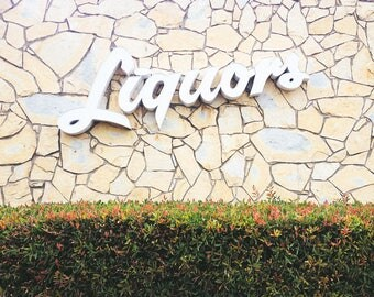 Oversized wall art photograph- Vintage Liquor Store Sign on a mid-century modern stone wall