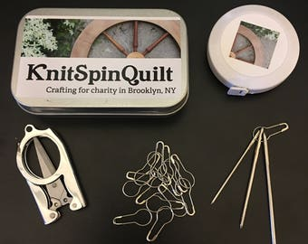 Knitting notions kit - folding scissors, yarn needles, measuring tape, locking stitch markers all nestled in a clamshell metal tin