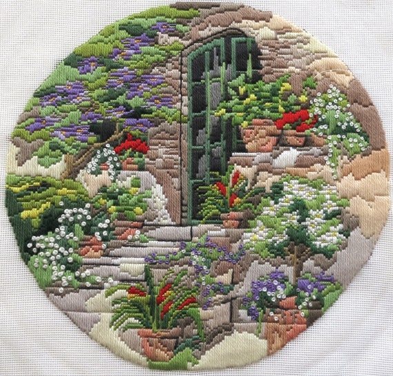 Completed embroidery on canvas, long stitched scene of beautiful garden with flowers and trees, circle, 12 inches / 30.5 cm across