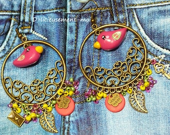 Earrings in bronze metal with a red kawaii bird made with polymer clay, beads and charms