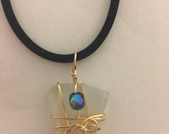 Clear beach glass necklace wrapped in gold wire with single black bead