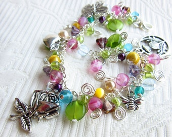 Garden lovers silver charm bracelet with flowers, a bee, butterfly and colorful beads. Silver charms