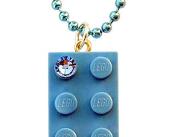 Light Blue LEGO (R) brick 2x4 with a Blue SWAROVSKI crystal on a Silver/Gold plated trace chain or on a Blue ballchain