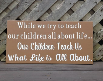 While We Try To Teach Our Children All About Life Wood and Vinyl Sign - Golden Brown and White