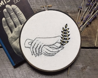 Hands holding golden fern embroidery
