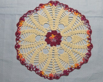 Doily featuring colorful flower and 'pineapples', hand-crocheted