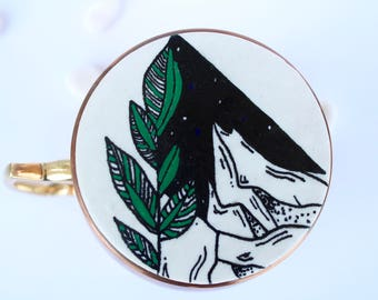 One - white, black, and green hand drawn triangle polymer clay coaster - mountains, leaf, abstract - 3.2 inches in radius.