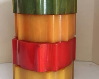 Four varied coloured bakelite napkin rings in muted green orange and yellow colours