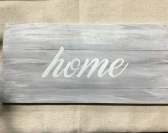 Weathered gray 'home' sign hand painted in creamy white