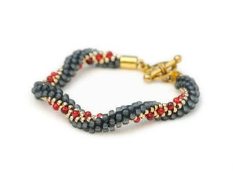 Beaded kumihimo bracelet - matte gray and gold with red drops and a toggle clasp - twisted spiral/curly shape