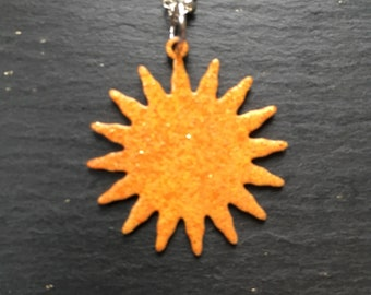 Enamelled sun pendant in vibrant oranges and yellows, on a silver chain